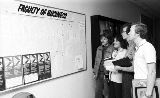 Faculty of Business students checking a bulletin board, October 1977.